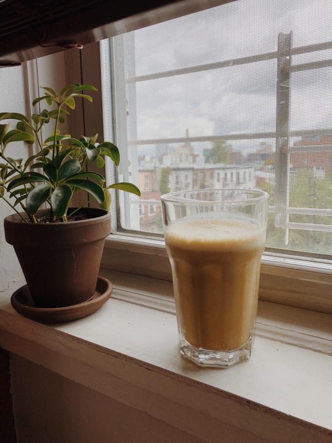 iced matcha turmeric latte on windowsill